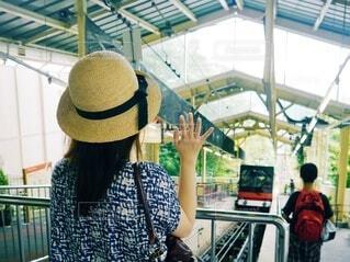 去っていくロープウェイに手を振る麦わら帽子の女性の写真・画像素材[4750510]