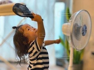 扇風機とハンディファンをダブル使いする小さな女の子の写真・画像素材[4769365]