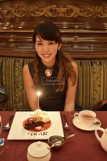 一杯のコーヒーをテーブルに座っている女性の写真・画像素材[854482]