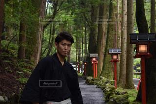 木の隣に立っている男の写真・画像素材[906770]