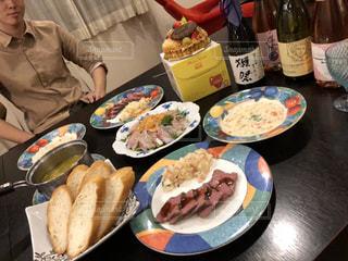 食品のプレートをテーブルに座っている女性の写真・画像素材[934284]