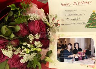 赤い花とテーブルに座っている人のグループの写真・画像素材[934300]