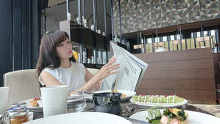 食品のプレートをテーブルに座っている女性の写真・画像素材[1175694]