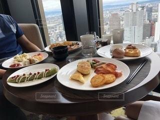 食品のプレートをテーブルに着席した人の写真・画像素材[1175695]