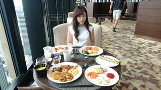 食品のプレートをテーブルに着席した人の写真・画像素材[1184689]