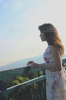 フェンスの前に立っている女性の写真・画像素材[1259922]