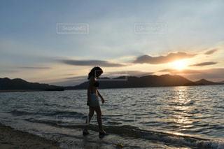 水の体の近くのビーチに立っている人の写真・画像素材[1310127]