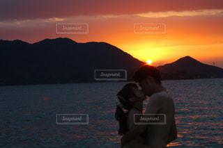 水の体の上に日没の前に座っている男の写真・画像素材[1310162]