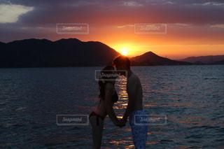 男の長い髪と体水に沈む夕日の写真・画像素材[1310165]