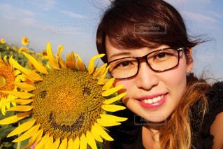 黄色の花の前に立っている女性の写真・画像素材[1354906]