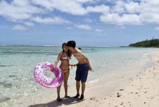砂のビーチでフリスビーを持っている人の写真・画像素材[1385455]