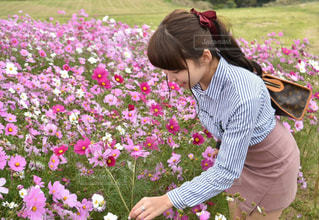 花の前に立っている人の写真・画像素材[1454490]