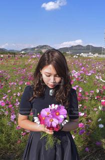 花の前に立っている人の写真・画像素材[1558370]