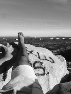 岩のビーチに立っている人 - No.825411