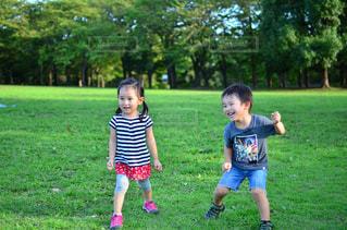 緑豊かな緑のフィールドに立っている少年の写真・画像素材[756232]