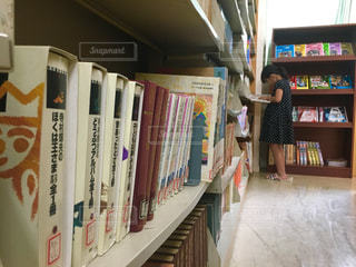 書店の棚の横に立っている人の写真・画像素材[743720]