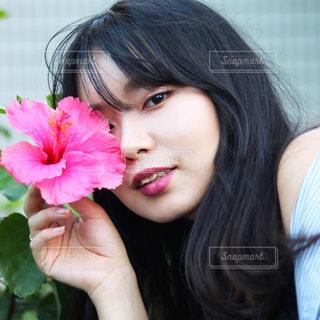 近くにピンクの花の女の子のアップの写真・画像素材[1417448]