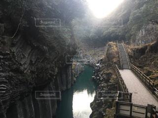背景の山が付いている水の体の上の橋の写真・画像素材[1027547]
