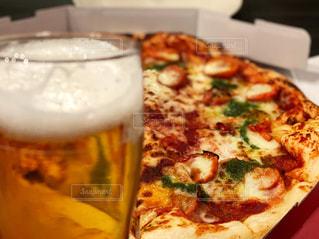 テーブルの上に座っているピザの写真・画像素材[3181605]