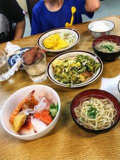 食品のプレートをテーブルに座っている人々 のグループの写真・画像素材[897437]