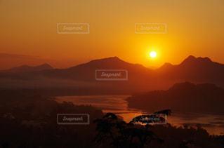 背景の山が付いている水の体に沈む夕日 - No.956052