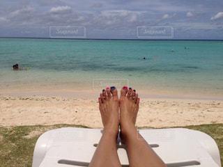 海の横にある砂浜のビーチの上に座っている男 - No.710266