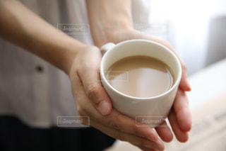 近くに一杯のコーヒーを保持している人のの写真・画像素材[1266754]