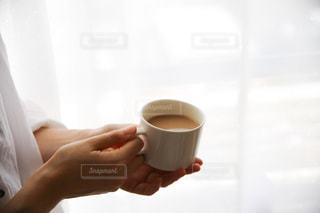 一杯のコーヒーを保持している人の写真・画像素材[1266764]