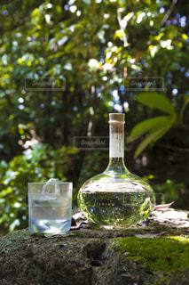 ワインのグラスの横に座っての花で一杯の花瓶の写真・画像素材[1282332]