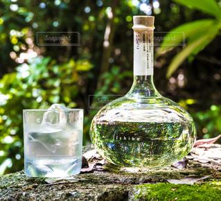 テーブルの上に座っての花の花瓶の横にガラスの瓶の写真・画像素材[1282625]