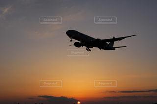 夕焼けに染まった空とヒコーキの写真・画像素材[2884250]