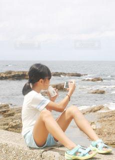海を撮影する少女の写真・画像素材[1386902]