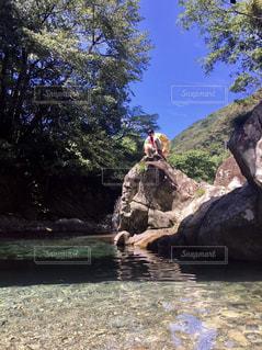 水の体の横にある岩の上の人々 のグループの写真・画像素材[708918]