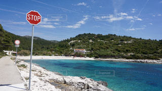 砂浜の上に座っている赤い停止記号の写真・画像素材[708937]