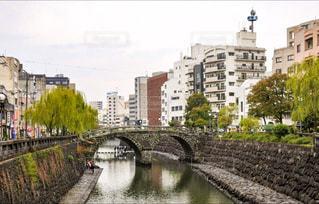 都市の川に架かる橋を渡る列車の写真・画像素材[867250]