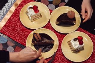 皿の上のケーキをテーブルに着席した人の写真・画像素材[934929]