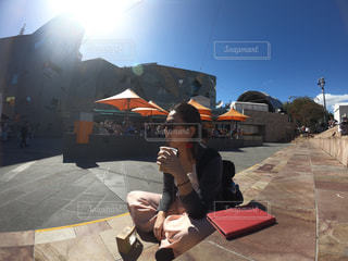 歩道の上に座っている人の写真・画像素材[1113021]
