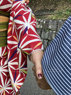 赤い傘を保持しているストライプのシャツの人の写真・画像素材[1587858]