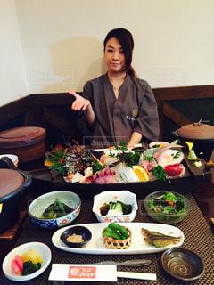 食品のプレートをテーブルに座っている女性の写真・画像素材[753352]