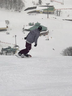 雪をスノーボードに乗る男覆われた斜面の写真・画像素材[1715388]