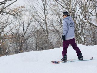 雪をスノーボードに乗る男覆われた斜面の写真・画像素材[1715395]