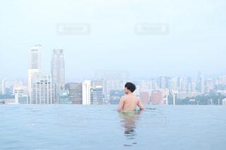 バック グラウンドで市と水体に坐っていた男の写真・画像素材[916035]
