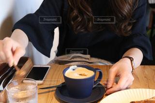 一杯のコーヒーをテーブルに着席した人の写真・画像素材[986169]