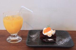 テーブルの上のコーヒー カップの横にあるオレンジ ジュースのガラスの写真・画像素材[1229839]