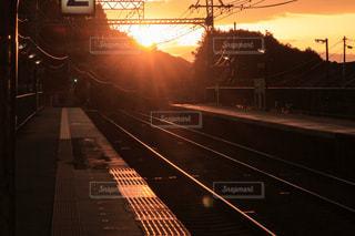 空,夕日,カメラ女子,太陽,駅,電車,夕暮れ,撮影,オレンジ,光,旅行,旅,ホーム,一眼レフ,日暮れ,日没前
