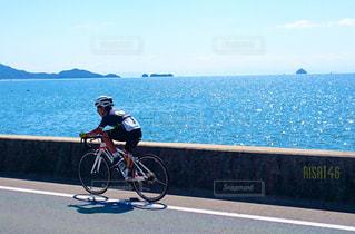 水の体の横に自転車に乗る男の写真・画像素材[720091]
