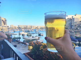 テーブルにビールのグラスを持っている手の写真・画像素材[742147]