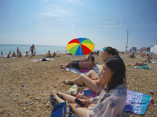 砂のビーチ パラソルで座っている女の子の写真・画像素材[825708]