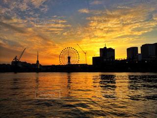 バック グラウンドで市と水体に沈む夕日の写真・画像素材[964389]