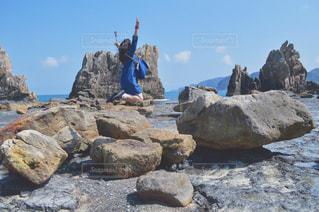 岩の上に空気を通って飛んで男の写真・画像素材[1136864]